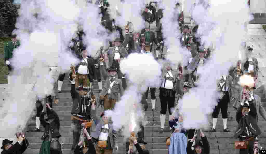 Bavarian riflemen and women in traditional costumes fire their muzzle loaders in front of the 'Bavaria' statue on the last day of the Oktoberfest beer festival in Munich, southern Germany.