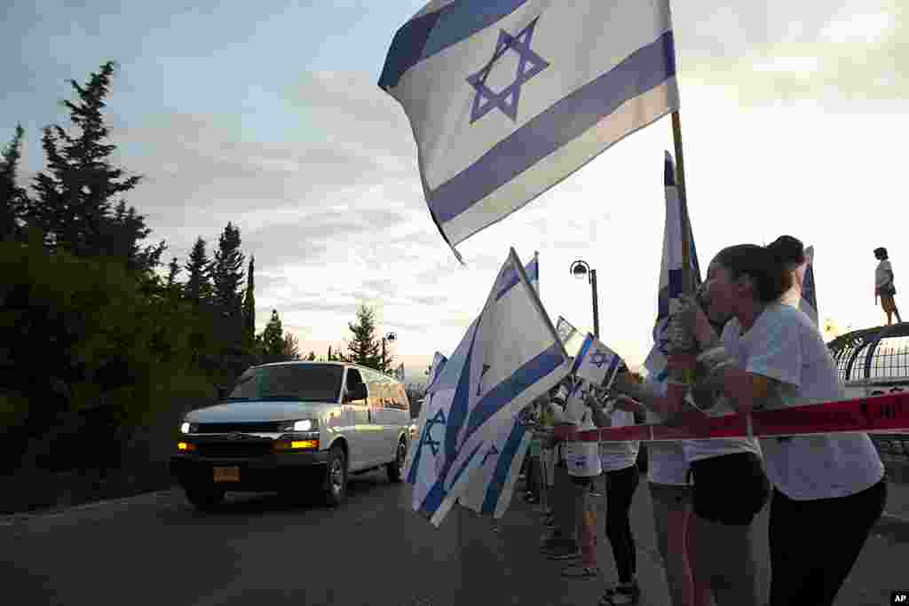 Residents wave flags and cheer as a vehicle carrying released Israeli soldier Gilad Schalit arrives in Mitzpe Hila, northern Israel, October 18, 2011. (AP)