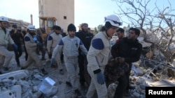 Nhân viên cứu hộ khiêng thi thể nạn nhân ra khỏi đống đổ nát của bệnh viện ở tỉnh Idlib, miền bắc Syria, sau vụ pháo kích ngày 15 Tháng 2, 2016.