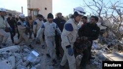 Warga dan relawan mengangkut korban dari reruntuhan rumah sakit yang dikelola oleh organisasi bantuan Medecins Sans Frontieres (MSF) atau Dokter Tanpa Tapal Batas - yang hancur terkena misil di Marat Numan, Idlib, Suriah (16/2). PBB mengumumkan konvoi bantuan sedang dikirim ke kota-kota yang terkepung.