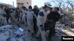 People and Civil Defense members carry a dead body removed from a destroyed Medecins Sans Frontieres (MSF) supported hospital hit by missiles in Marat Numan, Idlib province, Syria, Feb. 16, 2016.
