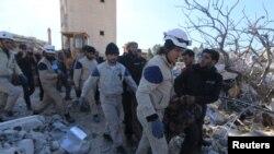 Warga sipil dan relawan membantu pencarian korban dari reruntuhan bangunan rumah sakit di Marat Numan, propinsi Idlib, Suriah yang hancur akibat serangan udara (16/2).