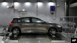 FILE - A Ford Focus is tested in heavy rain and wind in a testing room at the brand new Ford Environmental Test Center in Cologne, May 17, 2018.