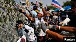 Para demonstran anti pemerintah memotong kawat berduri, sementara sebagian kecil dari mereka memasuki komplek kantor PM Thailand dan memutuskan aliran listriknya, Kamis (12/12).