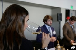 FILE: A woman tastes 2015 vintage wine tasting event January 25, 2018, in San Francisco.