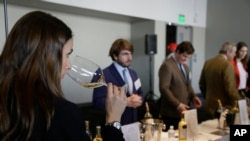 FILE - A woman tastes 2015 vintage wine from Barsac Sauternes during the Union des Grand Crus of Bordeaux tasting event January 25, 2018, in San Francisco.