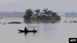 Indian villagers paddle a boat through floodwaters near partially submerged houses in Balimukh village in the Morigaon district of Assam state, Aug. 17, 2014.