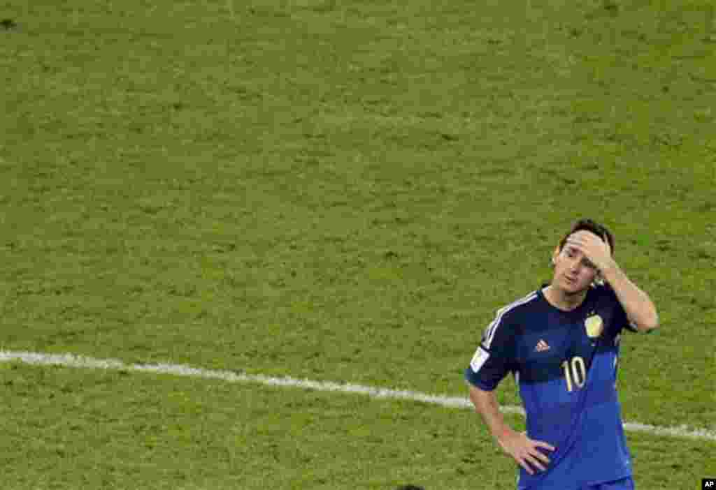 Reaksi bintang Argentina Lionel Messi saat para pemain Jerman merayakan kemenangan yang diraih dalam final Piala Dunia di stadion Maracana di Rio de Janeiro, Brazil, Minggu (13/7).(AP/Themba Hadebe)