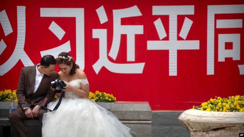 一對穿著婚禮服裝的夫婦2018年5月19日在北京觀看照相機背面的照片,身後是關於中國國家主席習近平的宣傳口號。