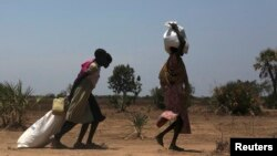 Women carry food at a food distribution site in Nyal, Unity State, April 1, 2014.