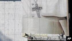 Pintores trabajan en un mural del papa Francisco en el costado de un edificio en la esquina de la calle 34 y la 8a. Avenida, en Nueva York.
