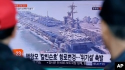 La gente ubicada en la estación de trenes de Seúl en Corea del Sur, ve un programa de noticias de televisión que muestra una imagen de archivo del portaaviones USS Carl Vinson.