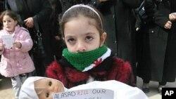 一名敘利亞的女孩星期天在大馬士革抱著一個洋娃娃﹐代表一名被殺的兒童
