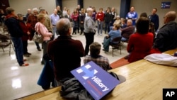 A campaign sign for Democratic presidential candidate Hillary Clinton sits behind a group of Clinton supporters during a Democratic party caucus in Nevada, Iowa, Feb. 1, 2016.