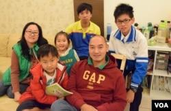 舉家移民台灣的香港人梁建忠(前左)與家人合照。(美國之音湯惠芸攝 )