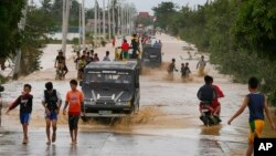 Residents wade through floodwaters fed by Typhoon Koppu at Zaragosa township, Nueva Ecija province, north of Manila, Philippines, Oct. 19, 2015.