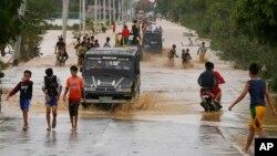 Warga menyeberang melaui banjir yang disebabkan oleh topan Koppu di kota Zaragosa, provinsi Nueva Ecija, Manila Utara, Filipina (19/10).