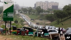 FILE - Cars line up to buy fuel at a petrol station in Abuja, Nigeria, Friday, April 1, 2016. Nigerian labor and civil society groups say their strike planned for Wednesday against a hike in fuel prices will go on as scheduled.