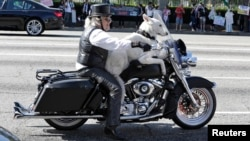 FILE - Jeremiah Gerbracht, a retired dog trainer, rides his Harley Davidson motorcycle with his dog on Wilshire Boulevard in Los Angeles, California.