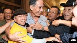 "Freed Vietnamese dissident Nguyen Van Hai (C) is greeted upon arrival at Los Angeles International Airport on October 21, 2014. The Vietnamese blogger, also known by his pen name ""Dieu Cay,"" was handed a 12-year prison sentence in September 2012 for conducting ""anti-state propaganda"" amid a crackdown on bloggers in the one-party state."