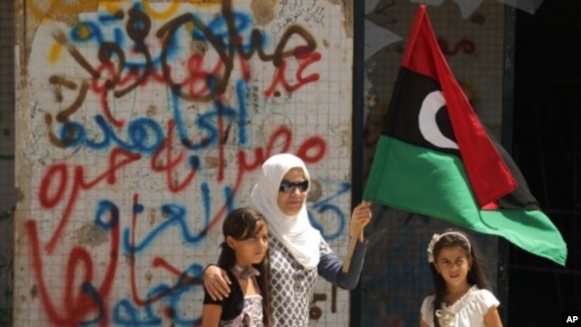 A Libyan woman holding the rebellion's flag tours with her daughters Moamer Kadhafi's destroyed headquarters of Bab al-Aziziya in Tripoli, August 31, 2011