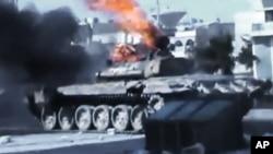 Imagen captada por un aficionado de un tanque sirio incendiado durante enfrentamientos con el ejército en Aleppo.