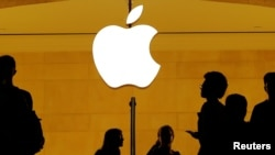 FILE - Customers walk past an Apple logo inside of an Apple store at Grand Central Station in New York, Aug. 1, 2018.