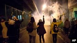 Manifestantes frente a la Universidad Amir Kabir en Teherán levantan flores mientras la policía dispara gas lacrimógeno el sábao 11 de enero. Foto: AP.