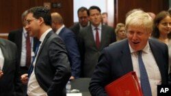 Newly appointed British Foreign Secretary Boris Johnson (R) arrives for the EU foreign ministers meeting at the EU Council building, in Brussels, Belgium, July 18, 2016.