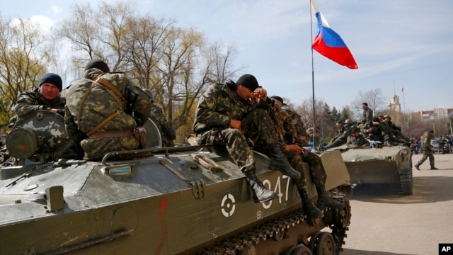 Combat vehicles with a Russian flag on one of them and gunmen on top are parked in downtown of Slovyansk, Ukraine, April 16, 2014.