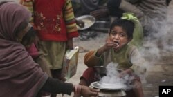 An Indian homeless child eats food as his mother cooks by a road side on a cold and foggy morning in Allahabad, India, Tuesday, Dec. 20, 2011.