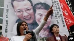 Manifestantes a favor del disidente Liu Xiaobo suben una foto con el Premio Nobel y su esposa en Hong Kong.