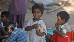 Indian street children eat food at a shanty town in Hyderabad
