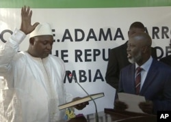 FILE - Adama Barrow, left, is sworn in as President of Gambia at Gambia's embassy in Dakar Senegal in this image taken from TV Thursday, Jan 19, 2017.