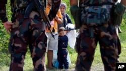 匈牙利士兵拦住一家希望从塞尔维亚进入匈牙利的移民或难民。 (2015年9月15日)