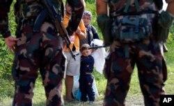 Binh sĩ Hungary chặn một gia đình người nhập cư tại lối ra biên giới giữa Serbia và Hungary, ngày 15/9/2015.