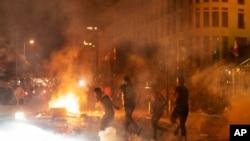 Polisi anti huru hara menembakkan gas air mata terhadap pengunjuk rasa anti-pemerintah, dalam aksi protes terhadap elit politik yang telah memerintah negara selama beberapa dekade, di Beirut, Lebanon, Jumat, 7 Agustus 2020. (Foto AP / Hassan Ammar)