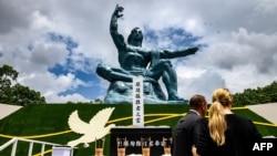 ناگاساکی پر امریکہ کی جانب سے ایٹم بم گرائے جانے کی 75 برسی کے موقع پر پیس پارک میں نصب مجسمہ آزادی کے سامنے لوگ کھڑے ہیں۔9 اگست 2020