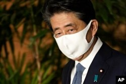 Japan's Prime Minister Shinzo Abe, wearing a face mask,walks after his press conference in Tokyo, Aug. 28, 2020.