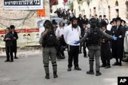 FILE - In this March 30, 2020, photo, ultra-Orthodox Jews gather during a protest against government's measures to stop the spread of the coronavirus in the Orthodox neighborhood of Mea Shearim in Jerusalem.