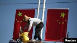 រូបឯកសារ៖ កម្មករព្យួរទង់ជាតិចិននៅលើផ្លូវនៅពេលមុនពេលការប្រារព្ធខួបលើកទី ៧០ នៃការបង្កើតសាធារណរដ្ឋប្រជាមានិត នៅខេត្ត Yunnan កាលពីថ្ងៃទី២២ ខែកញ្ញា ឆ្នាំ២០១៩។