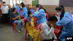 Para pelajar menerima vaksinasi COVID-19 di sebuah sekolah di Mumbai, India (6/9) (foto: ilustrasi).
