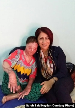 Sarah Said Haydar, left, shown here with a Yazidi activist, suffered burns over more than half her body in a suicide attempt.