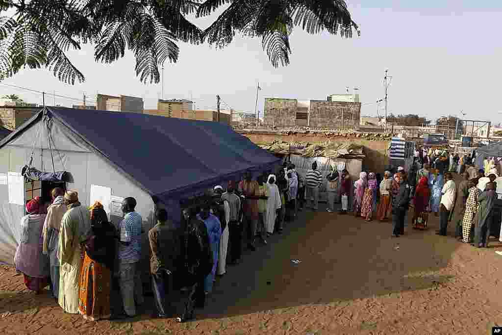 File d'attente des électeurs devant un bureau de vote du quartier Guediawaye, à Dakar (AP)