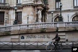 Un hombre en bicicleta sostiene una bandera francesa cerca del Arco del Triunfo en París durante una manifestación el sábado 1 de diciembre de 2018.