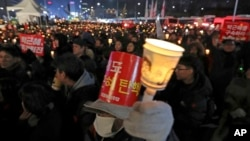 Protesters hold signs and candles during a rally demanding the resignation of South Korean President Park Geun-hye in Seoul, South Korea, Dec. 31, 2016.