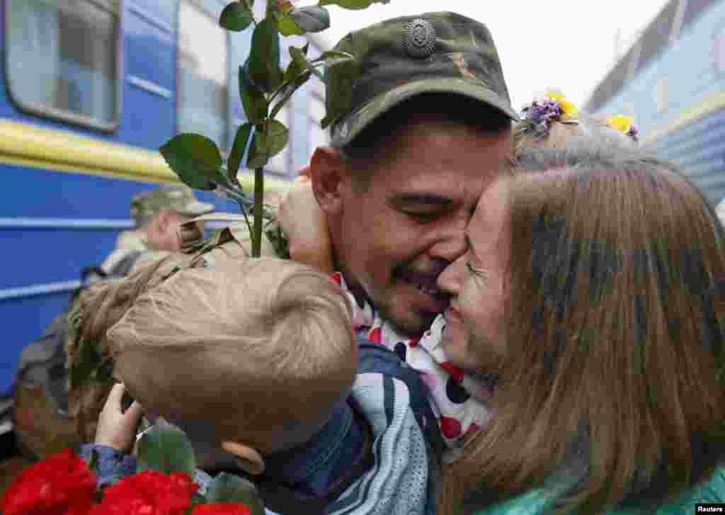 Seorang tentara Brigade Artileri 44 memeluk istrinya dan anaknya di stasiun kereta di Kyiv setelah kembali bertugas di Ukraina timur.