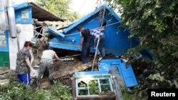 Cư dân địa phương dọn dẹp đống đổ nát do lũ lụt ở thị trấn Krymsk, miền nam nước Nga, 8/7/2012