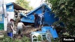 7月8日,俄羅斯南部克拉斯諾達爾地區的居民在一所北洪水毀壞的房子中幫助搜救工作。