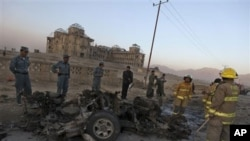 Afghan police officers inspect the remains of a vehicle used by a suicide bomber at the site on an explosion on the outskirts of Kabul, Afghanistan, Friday, Nov. 12, 2010. A suicide car bomber blew himself up as a NATO convoy passed by his vehicle on the